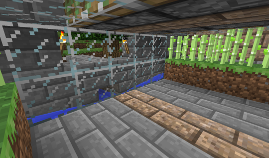 This screenshot is from beneath the pistons, between the two rows of sugar cane. On the outside of each row is a water canal. These two canals turn the corner at the end of the row and merge, eventually heading into the covered canal whose entrance you can see through the glass.